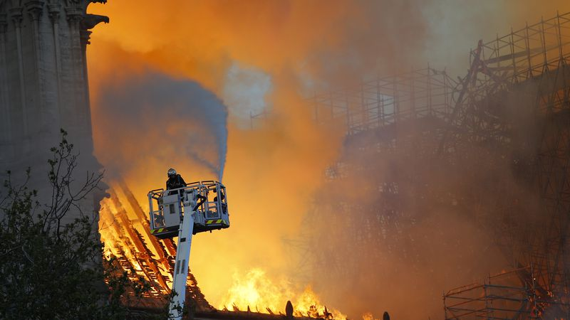 A firefighter uses a hose to battle the fire at Notre Dame cathedral on Monday. (AP...