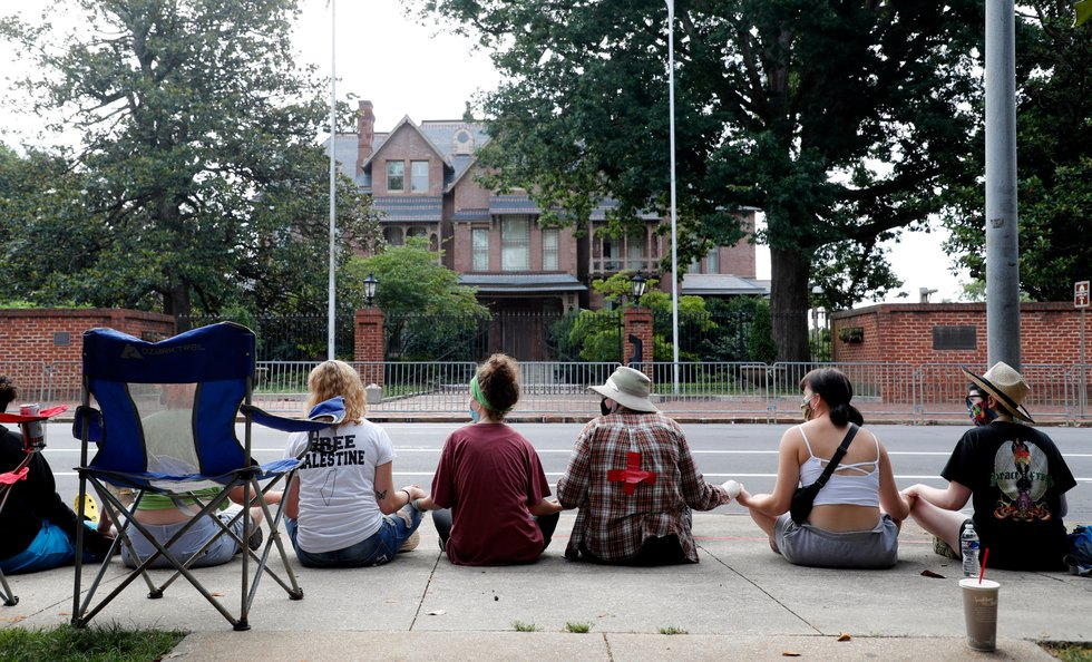 Protesters sit across the street from the N.C. Executive Mansion in Raleigh, N.C., Tuesday...