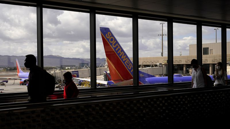 FILE - In this March 26, 2021 file photo, passengers walk past a Southwest Airlines plane at...