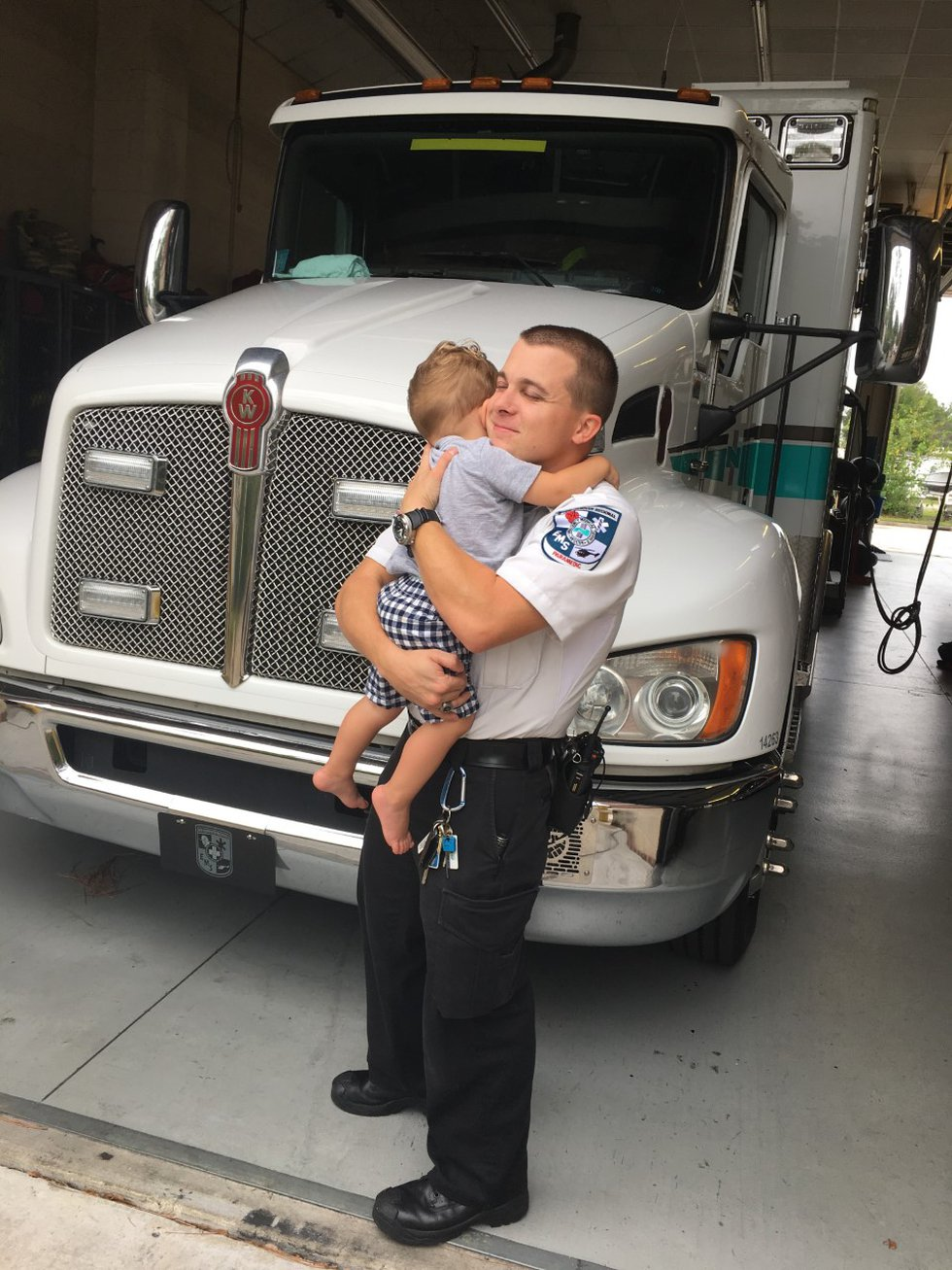 Caleb Camp, who works for New Hanover EMS, hugs his son Jackson, 1, before his shift which is...