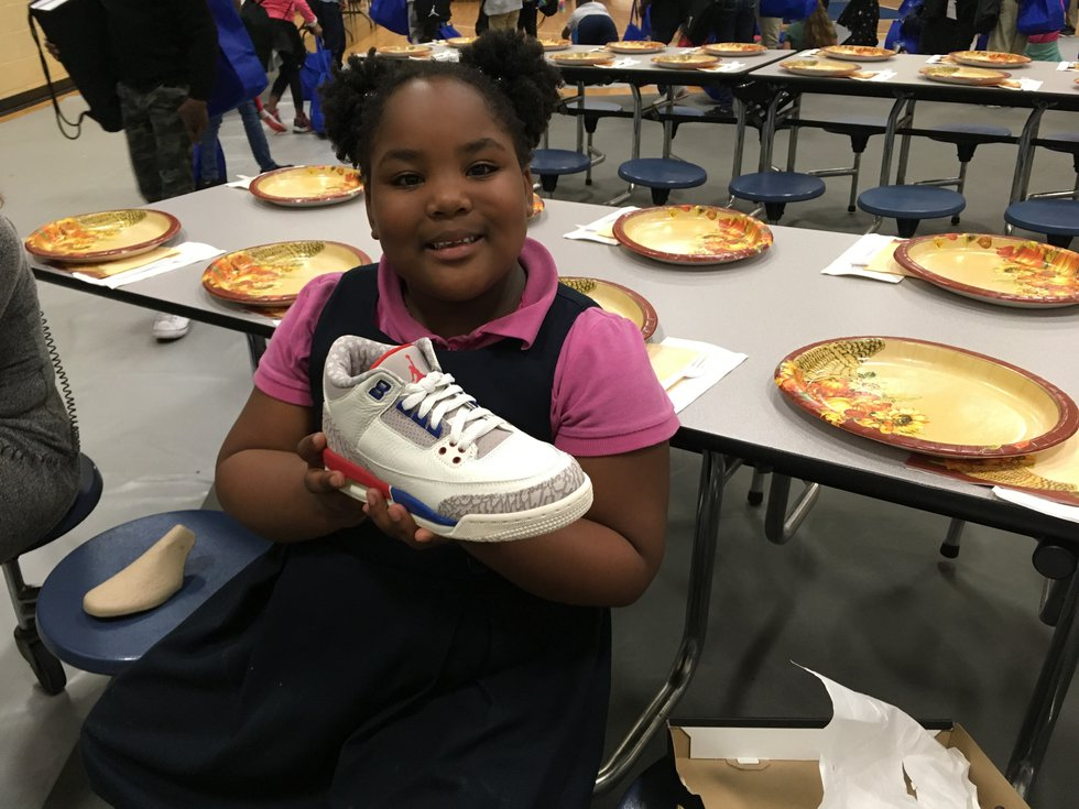 Brieyelle holds one of her new Air Jordan shoes Tuesday at the Community Boys and Girls Club in...