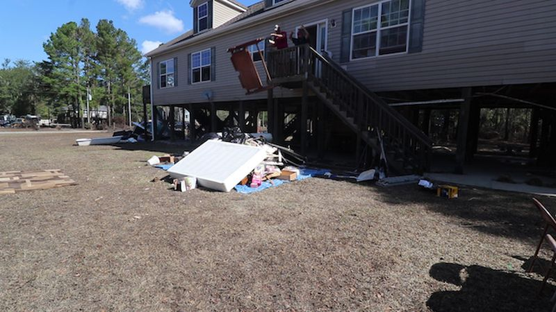 Neighbors help clean out houses in the Riverbend neighborhood in Burgaw after all but two homes...