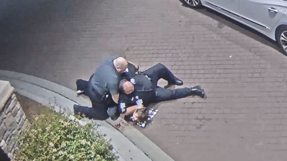 Security guards at Atrium Health - Lincolnton sit on top of a teenager after tackling him to...