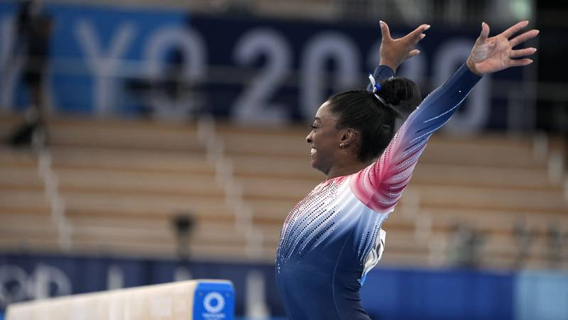 Simone Biles, of the United States, dismounts from the balance beam during the artistic...
