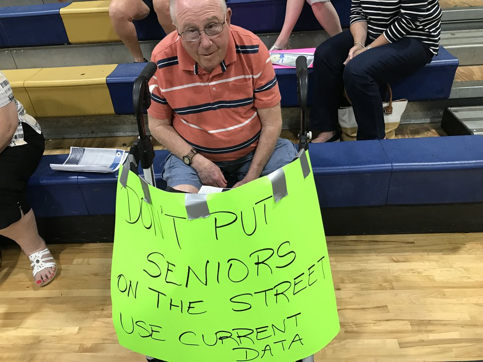 Don Florian displays a sign made by his wife, Rhonda, at Tuesday's open house and public...