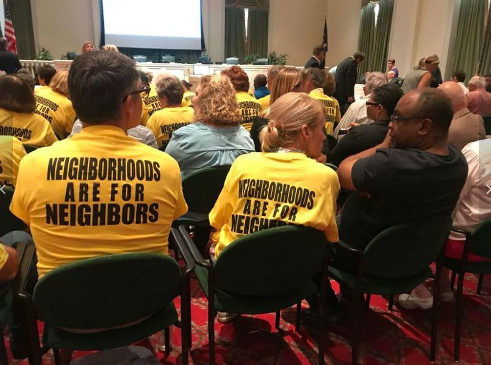 """Citizens against short-term rentals wore yellow """"Neighborhoods Are For Neighbors"""" T-shirts to..."""