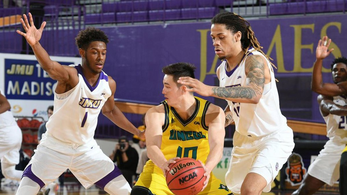 UNCW point guard Kai Toews, with ball, looks to pass while being guarded by a pair of James...