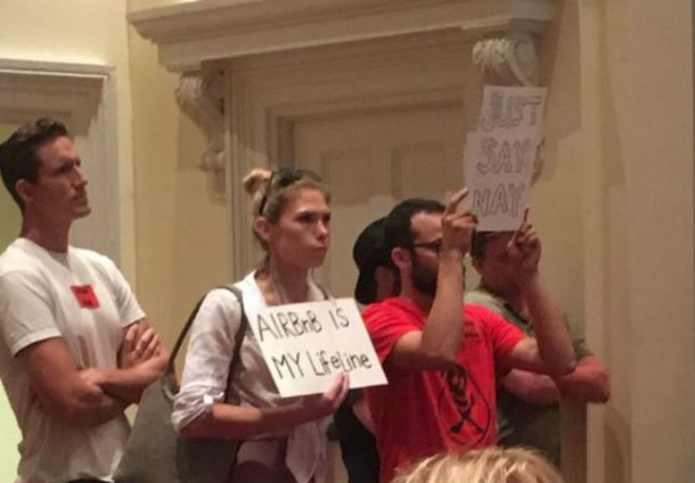 Some at Tuesday's meeting held signs for and against short-term rentals. (Source: WECT)