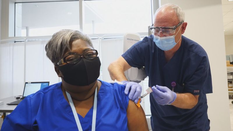 Karen Herring receives the first dose of the COVID-19 at New Hanover Regional Medical Center
