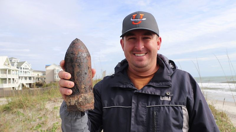 Bradley Dixon with a 27 lb projectile he dug up with his metal detector in Topsail Island....