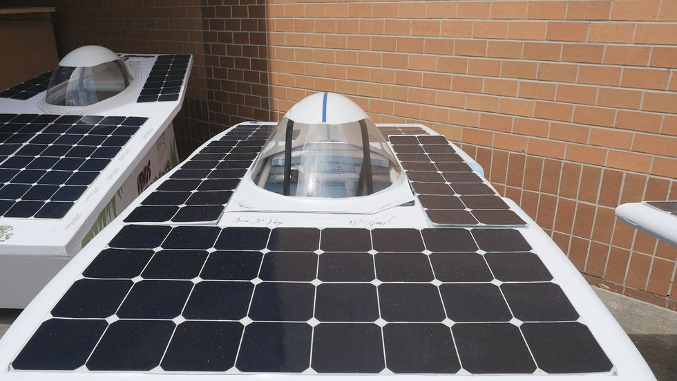 Black, square solar panels attached to the top of the cars' bodies provide power to the...