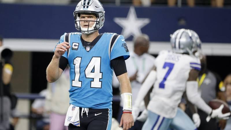 Carolina Panthers quarterback Sam Darnold walks to the sideline as Dallas Cowboys' Trevon Diggs...