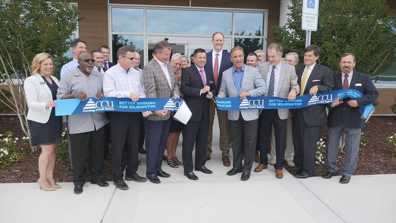 Corning Credit Union CEO Gary Grinnell, center, cuts the ribbon Wednesday morning in front of...