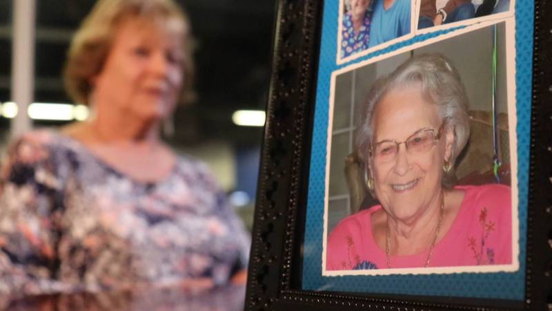 Renee Herwin (background) is seen with the picture frame she used to place a hidden camera in...