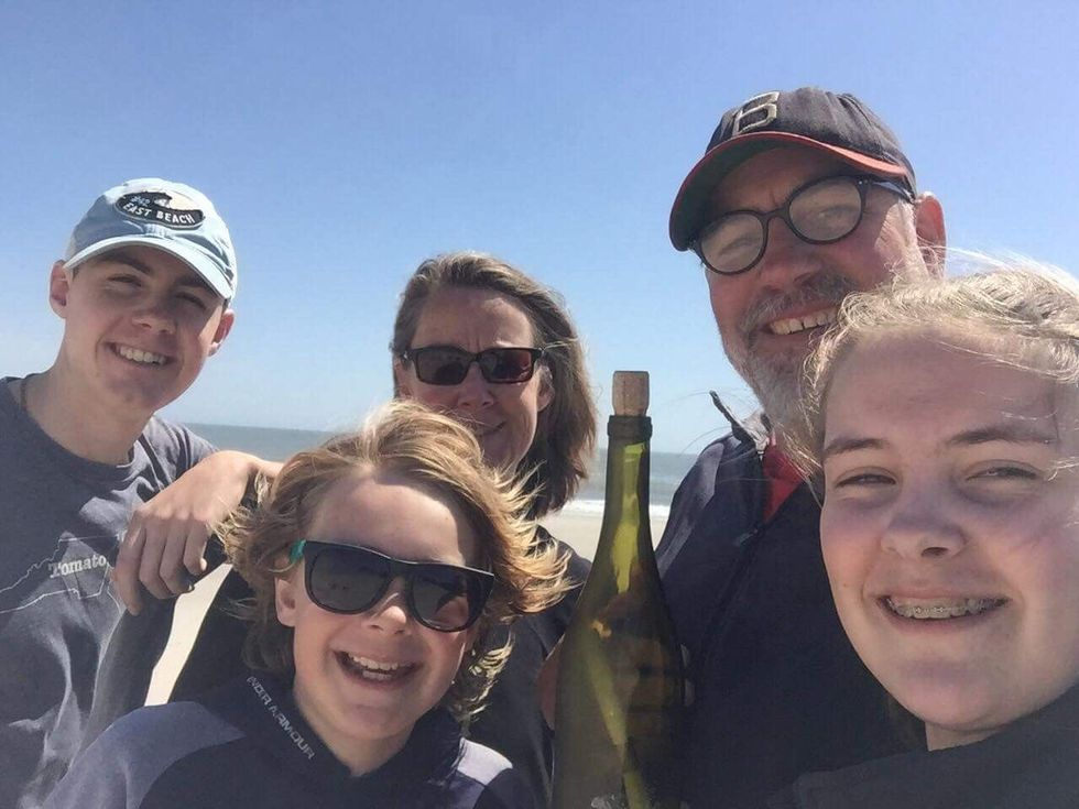 The Spalding family poses for a picture with the McGee family's message in a bottle. (Source:...