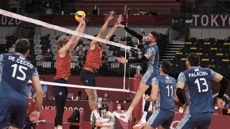 Argentina's Facundo Conte spikes a ball past Maxwell Holt, #12, and Taylor Sander, of the...