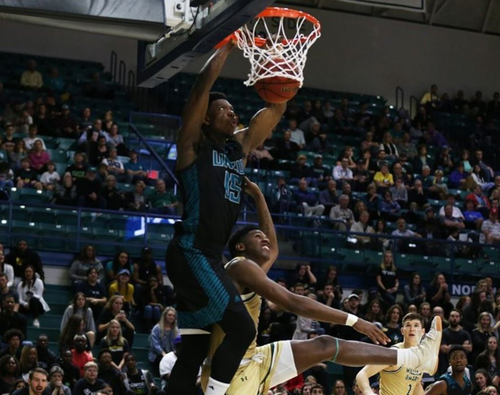 UNCW's Devontae Cacok dunks over a William & Mary defender on Thursday in Trask Coliseum....