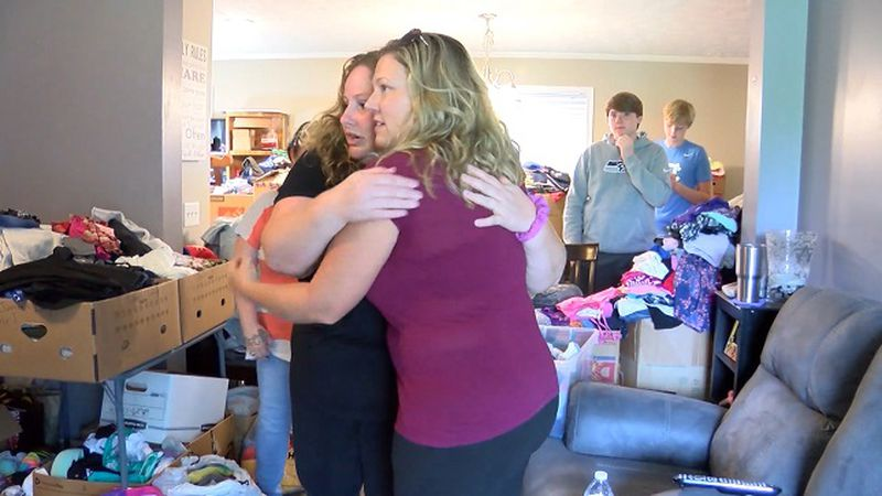 Sarah Prevatte hugs a friend in her home distribution center. (Source: WECT)