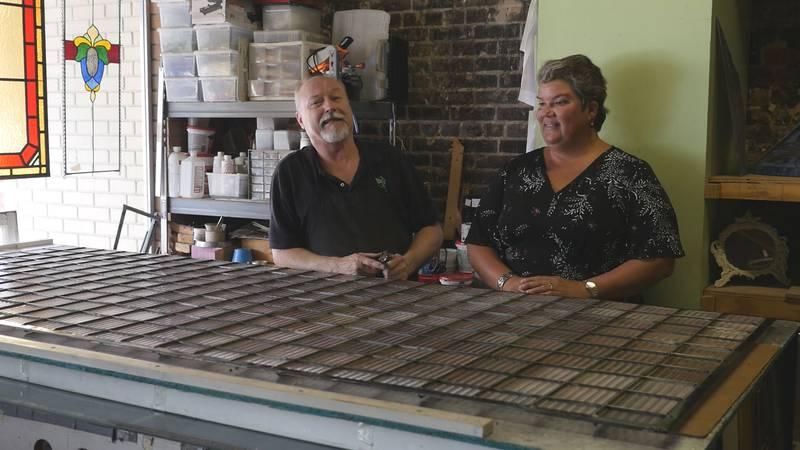 Bill McClanahan, left, and Mary Anne Hewett talk at Enchanted Realm, McClanahan's stained glass...