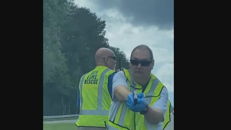 A video shows a firefighter pointing a gun at a driver.