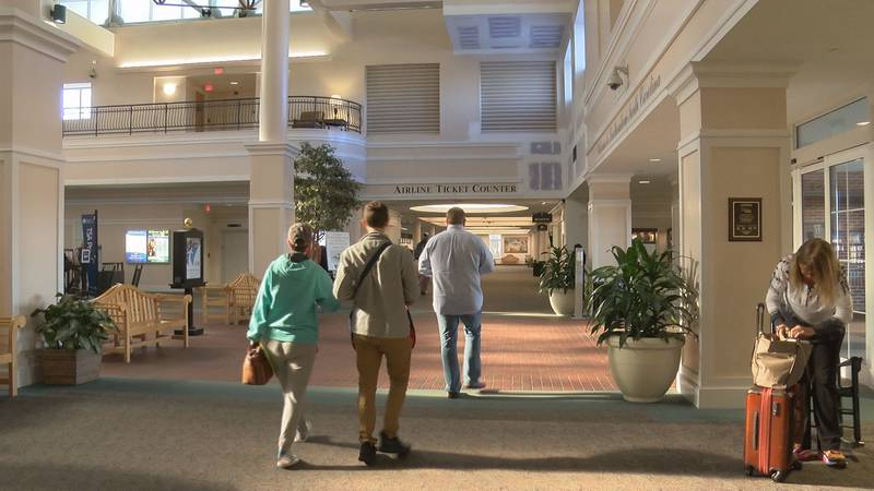 Passengers walk through the lobby of ILM. The airport is in the middle of a major expansion...